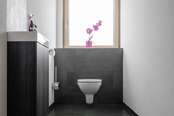 Fliesen Jams - Gäste WC, schwarze Fliesen, Waschbecken mit Unterbau, weisses Klo, modern, Neubau, Spiegel