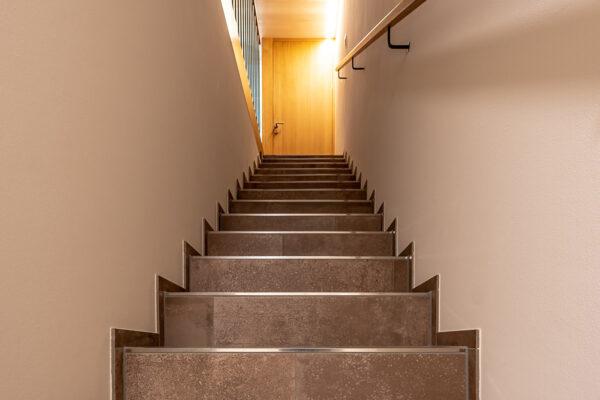 Fliesen Jams - Treppe, Türe, braune Fliesen, silbrige Kantenprofile, Geländer, Handlauf