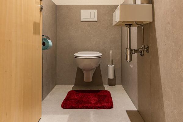 Fliesen Jams - WC, braune Fliesen, Waschbecken, Spiegel,